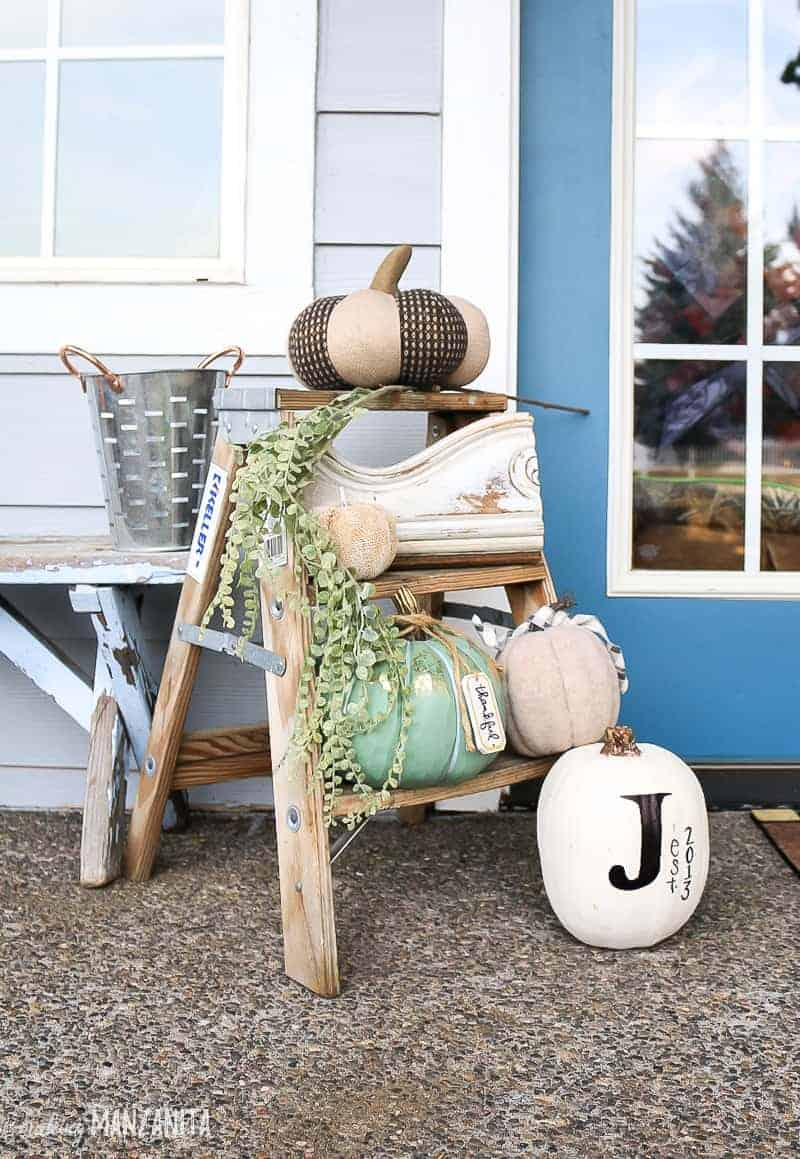 Small wooden step stool decorated with pumpkins for front porch for fall