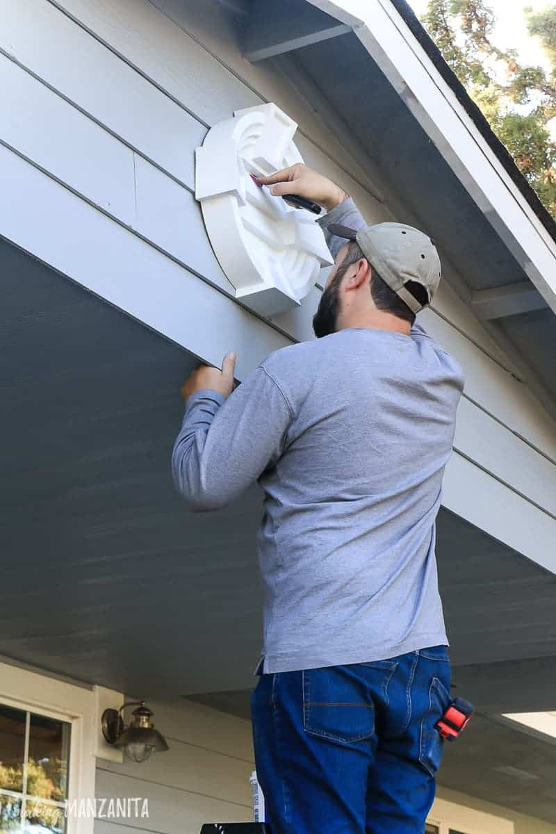 Man adding spackling to the front of a white round louver placed on the front of a house as gable decorations