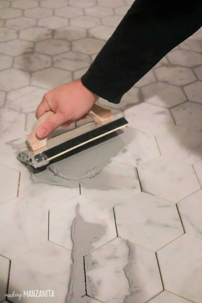 There is a hand using a float to push grout over the crack of white hexagonal tile cracks