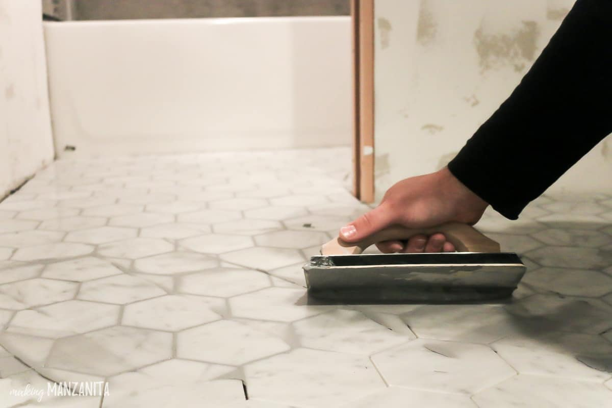 Man applying gray grout over marble tile flooring with rubber float held at a 45 degree angle in a bathroom