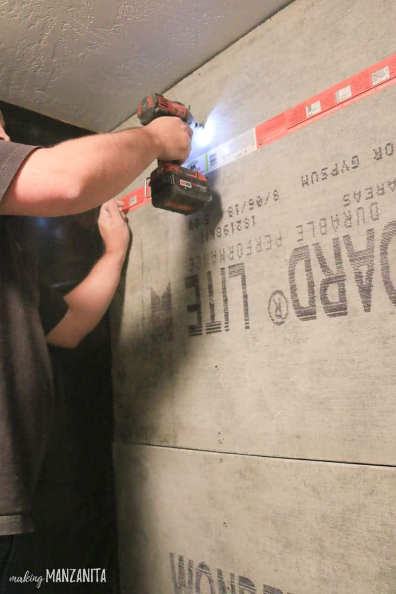 Man drilling screws into cement backer board in shower before doing shower tile installation