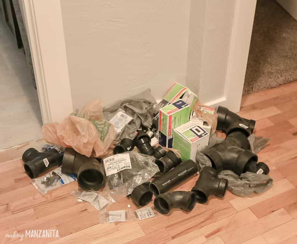 Pile of plumbing supplies in hallway
