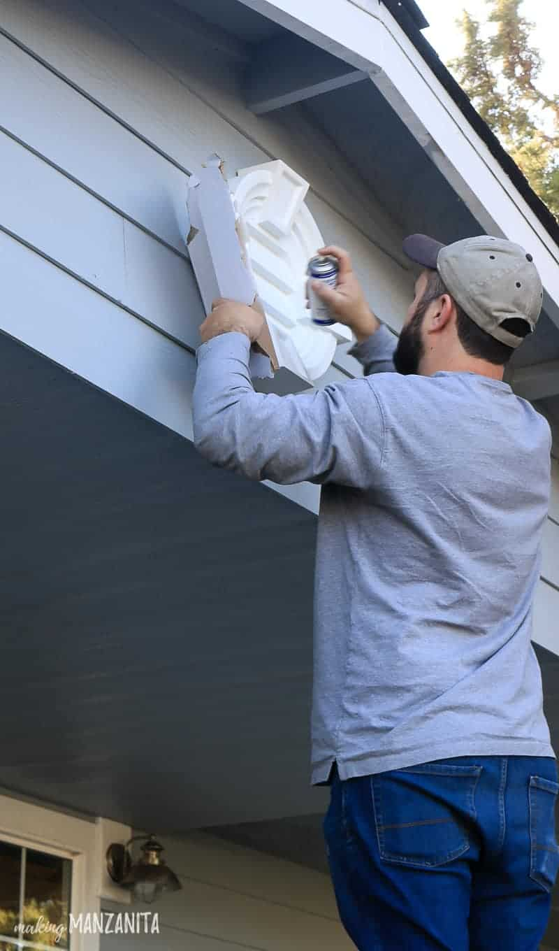 Man spray painting white louver that is attached to the front of a home