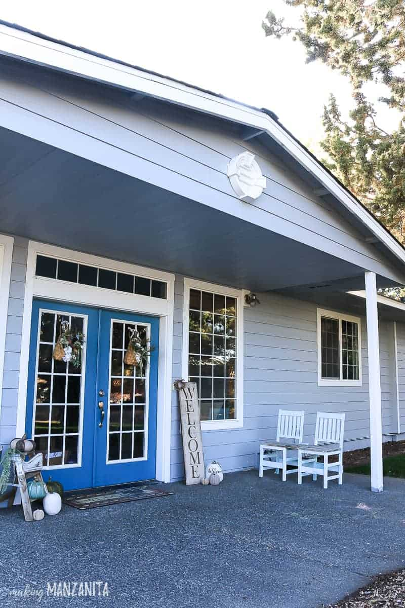 Side angle of front porch with roof overhang on a light blue house with white trim with added decorative louver to the gable area above the porch