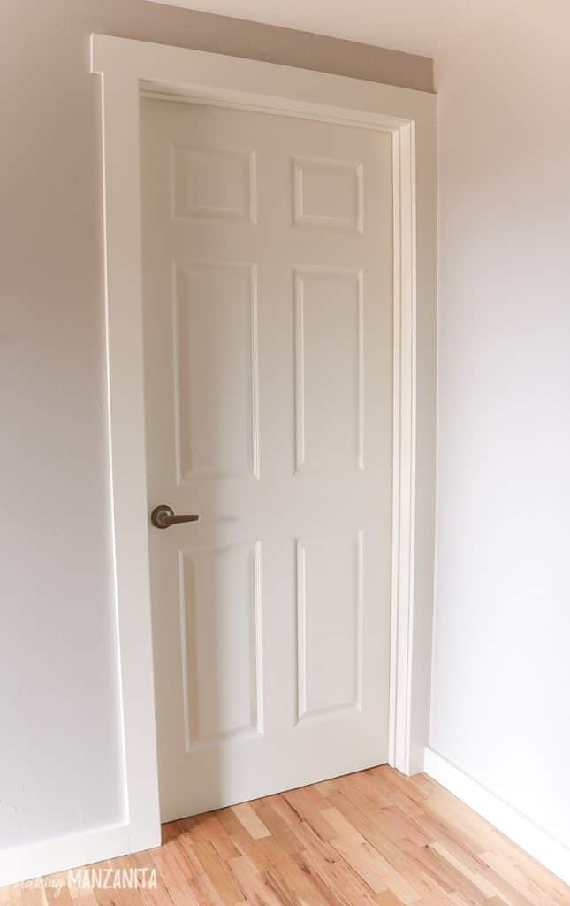 White 6 panel interior door with white trim and gray walls