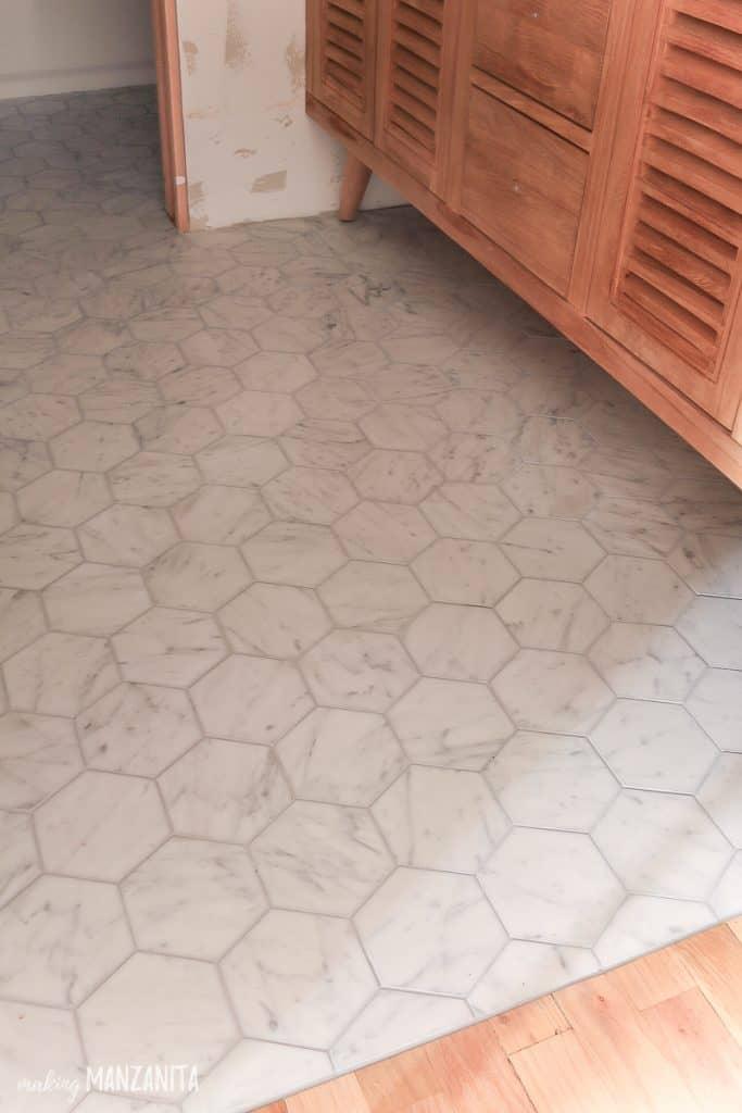 Hexagon marble tile flooring in front of wooden vanity in bathroom under renovation