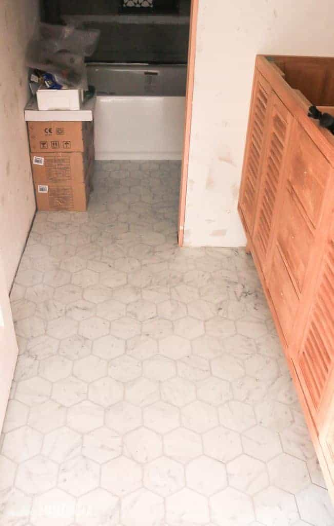Marble hexagon tile floors in bathroom under renovation with gray grout and wood vanity