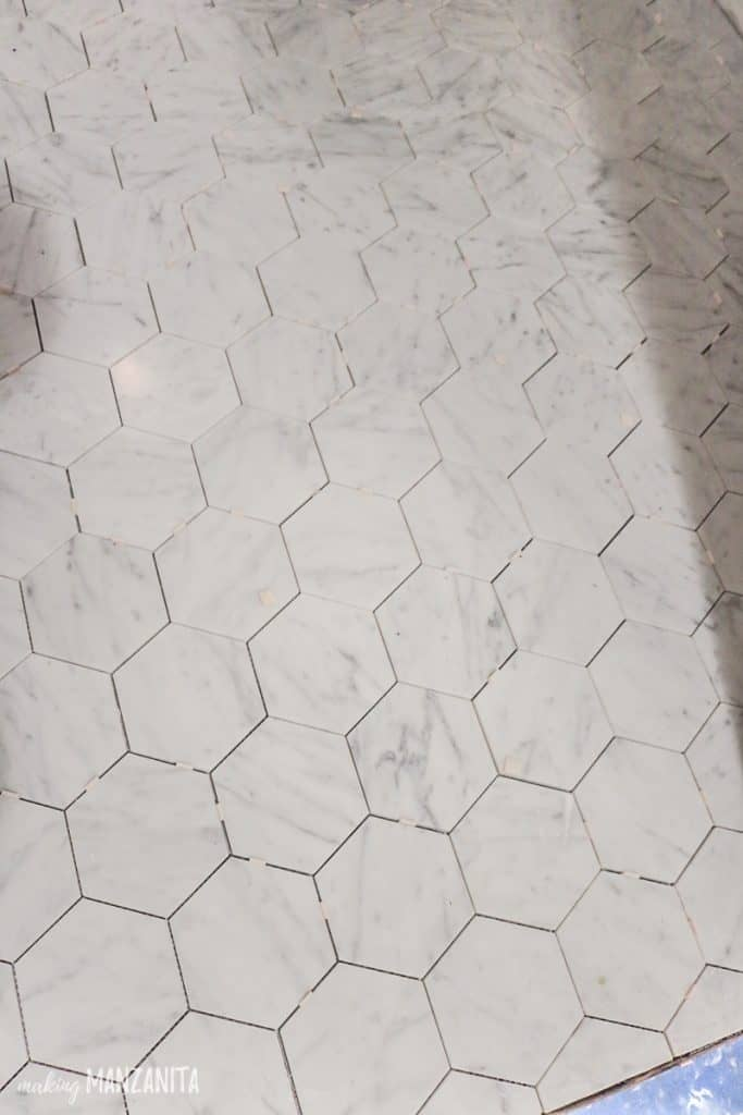 Hexagon tile flooring in bathroom while installing with spacers still in it and missing grout
