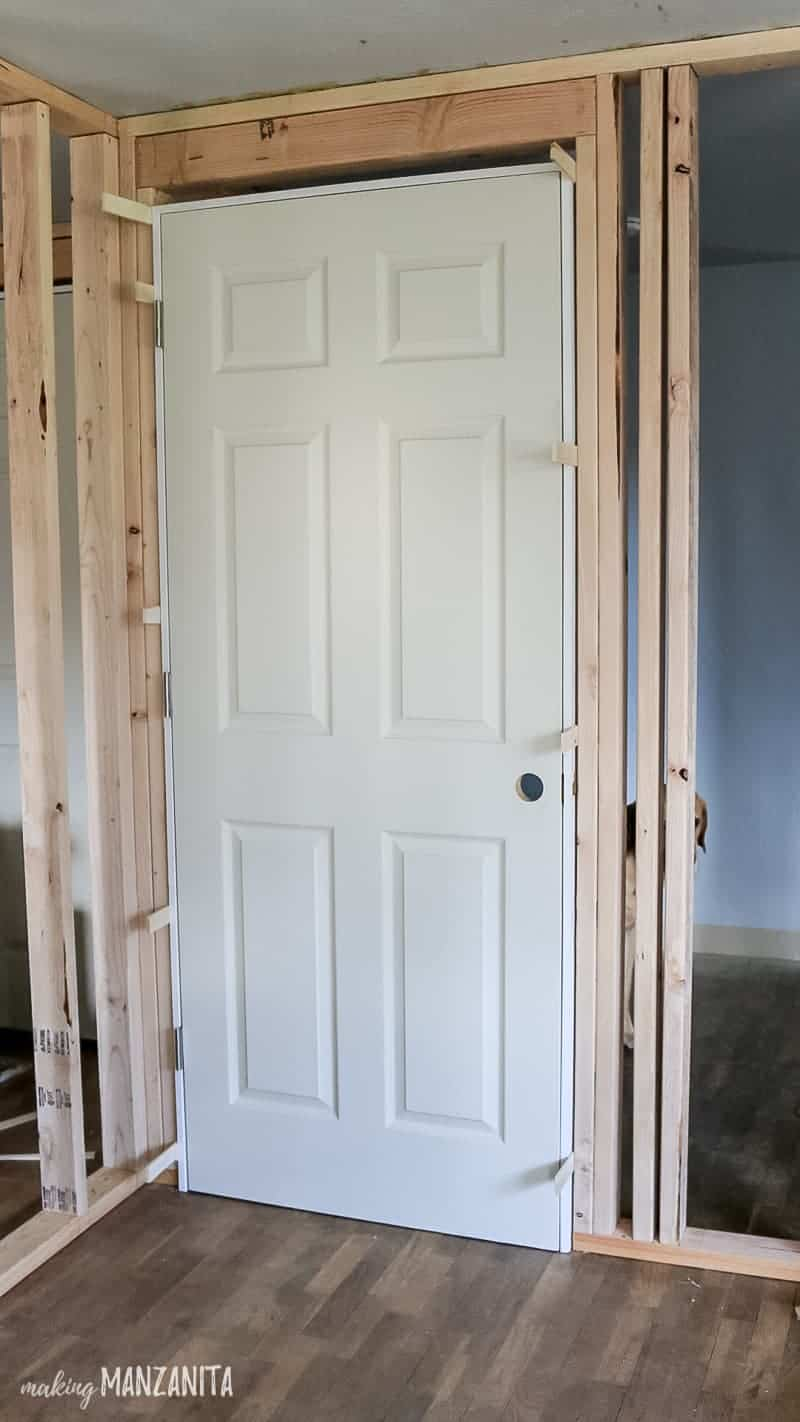 Prehung door in frame with shims added to the edges of the door