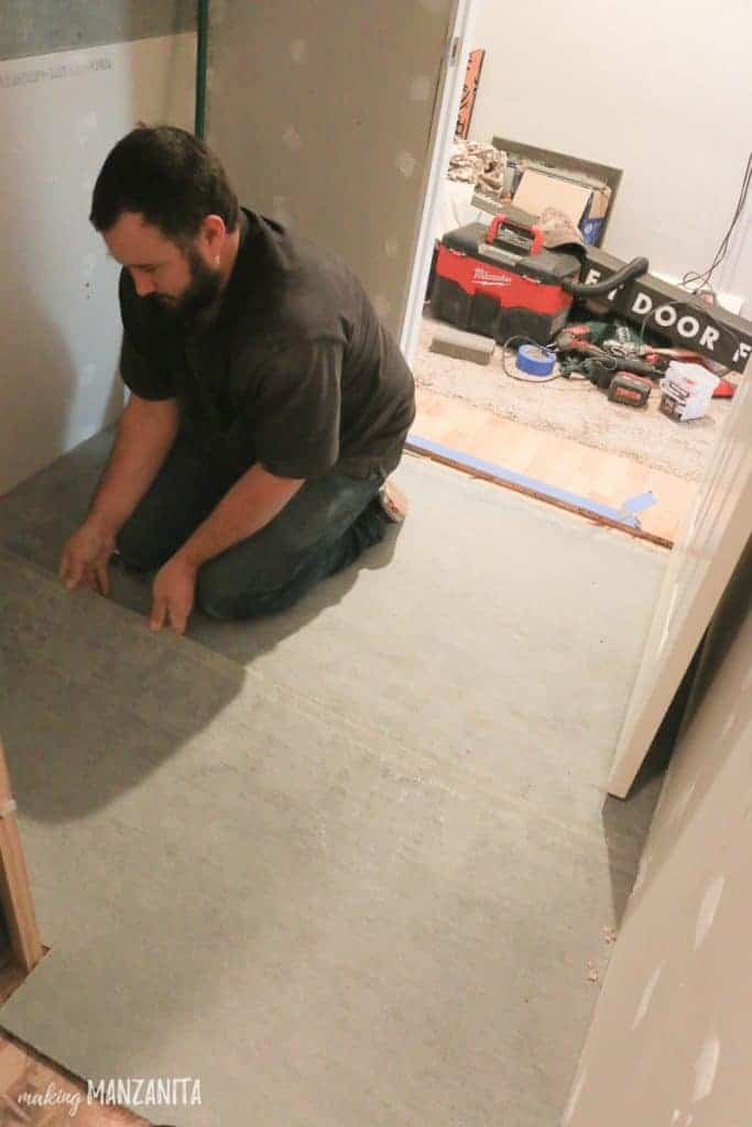 Man laying sheet of concrete backer board on floor before starting to tile the floor