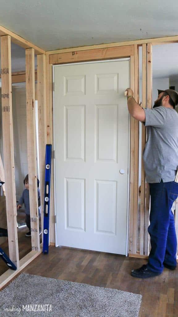 Man installing shims around a door frame
