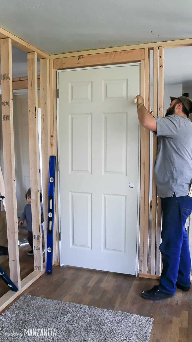 Man attaching the door to the wood wall frame