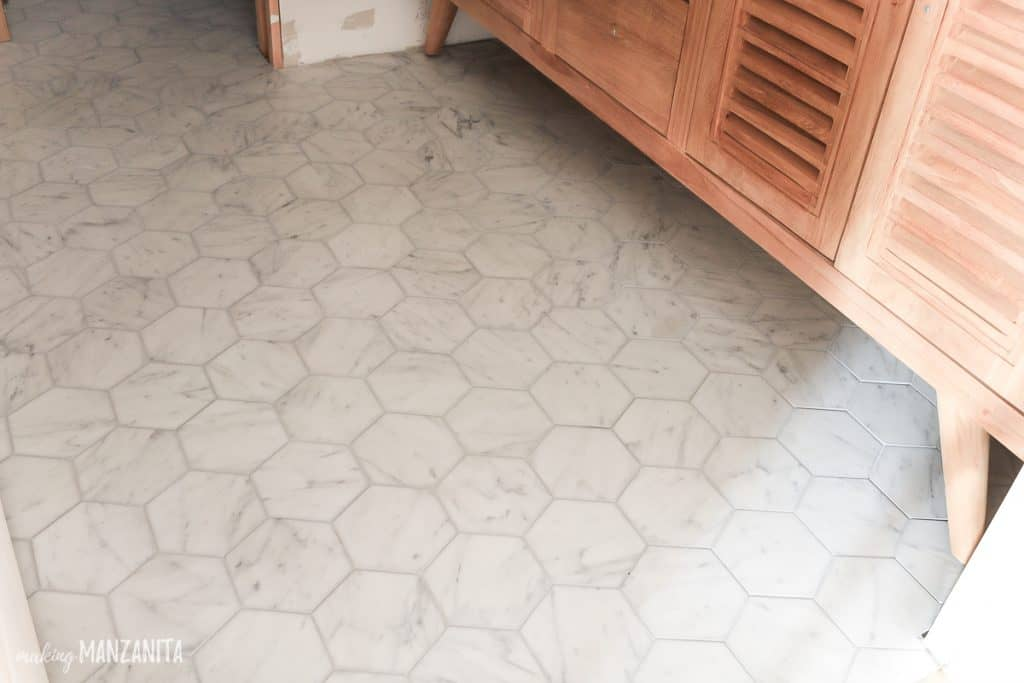 shows white marble hexagonal tile floors under a wood cabinet
