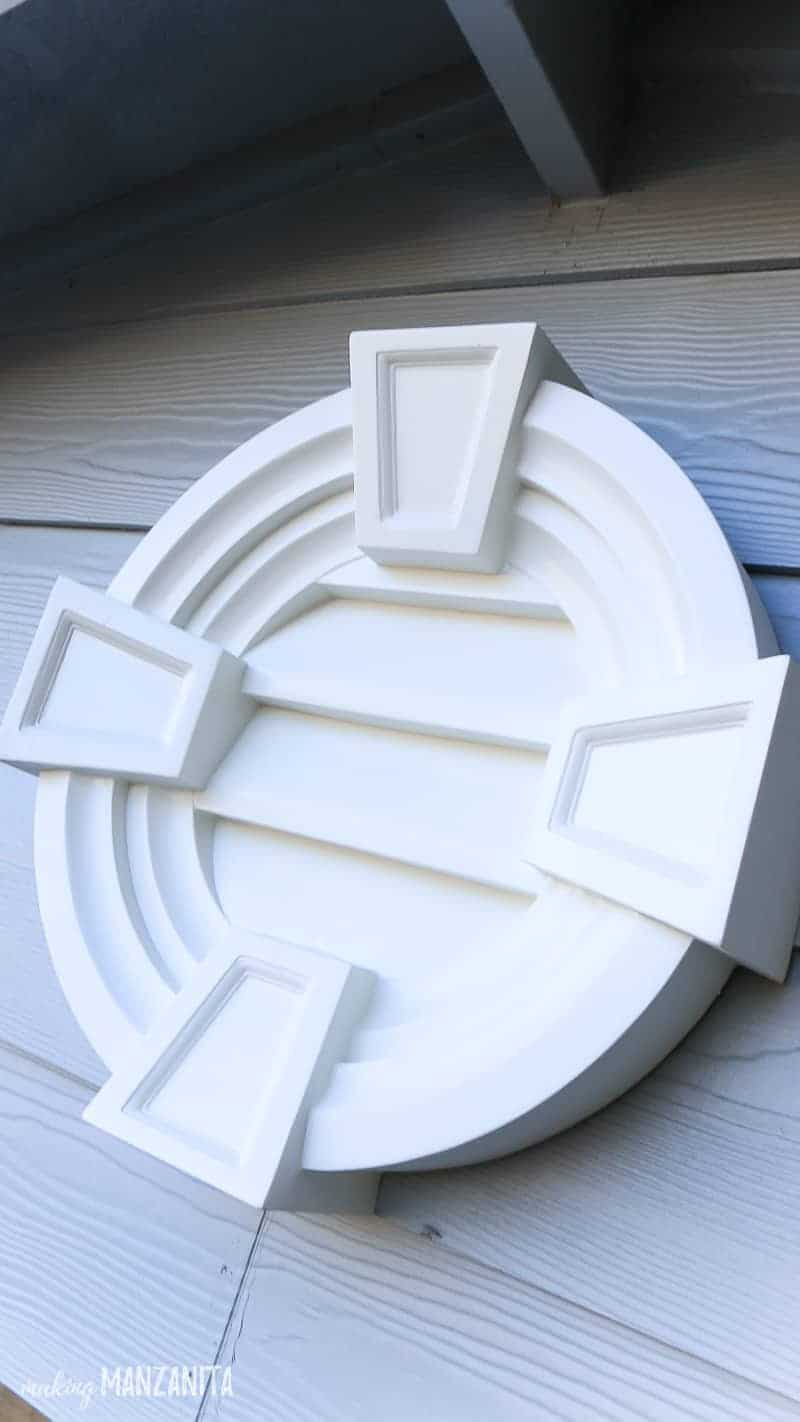 Close up shot of round decorative white louver attached to a light blue house