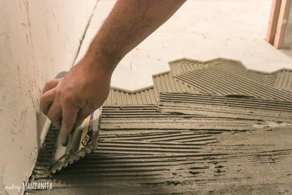 Applying thin set mortar with a trowel under tile flooring