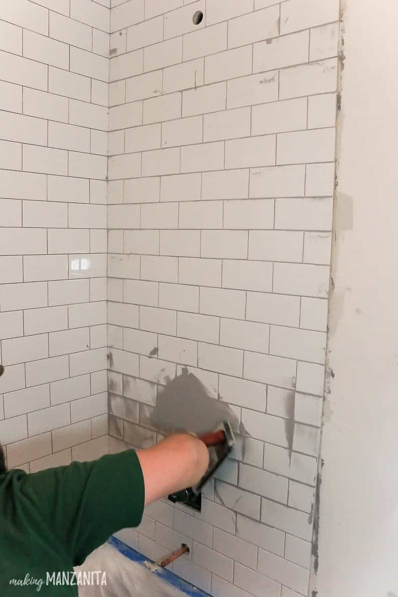 Man spreading gray grout over white subway tile in shower with rubber float