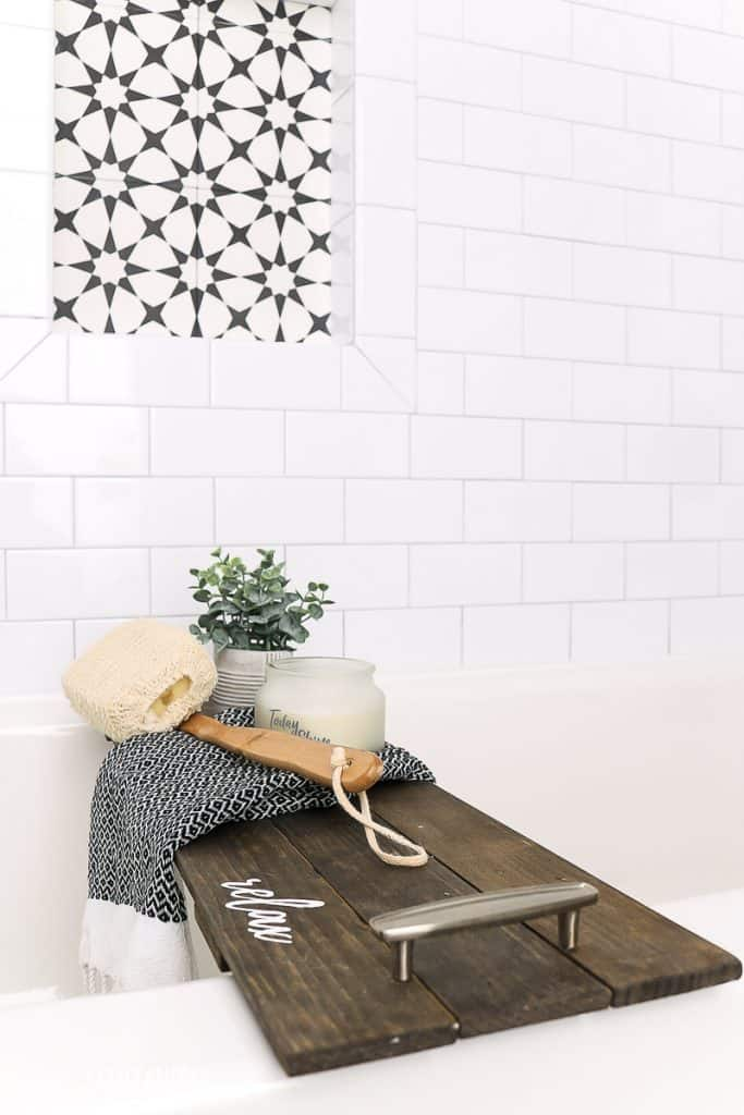 DIY bathtub tray on display in a boho farmhouse bathroom setting with loofah scrubber, black and white towel, candle and plant sitting on the tub shelf with a white bathtub featuring white subway tile and black and white patterned shower niche in the background