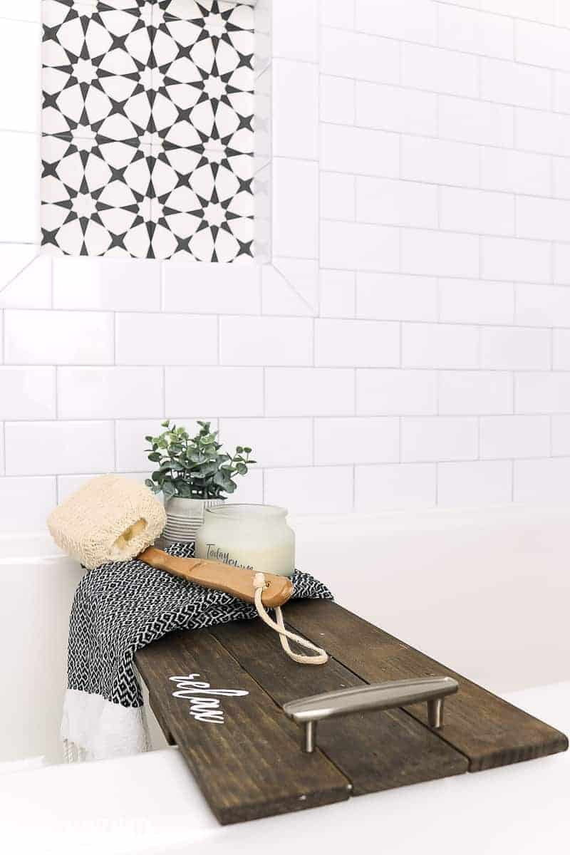 Wooden bath tub tray sitting in bright white bathtub with subway tile walls and shower niche with background of black and white subway tile