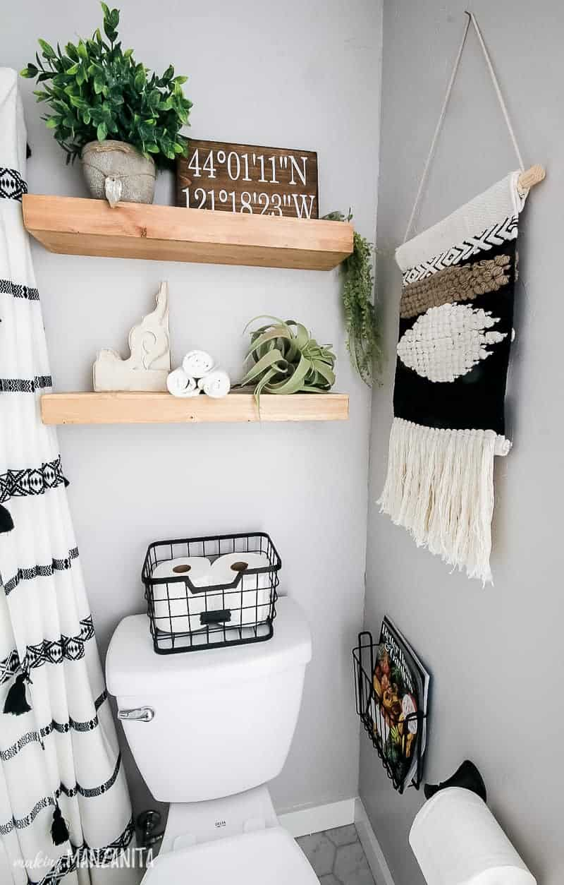 Water closet with light gray walls showing toilet with basket on top to hold toilet paper, magazines in wall basket, boho woven wall hanging, wood floating shelves with boho styled decor including faux plants, airplant, coordinates sign and wooden corbel