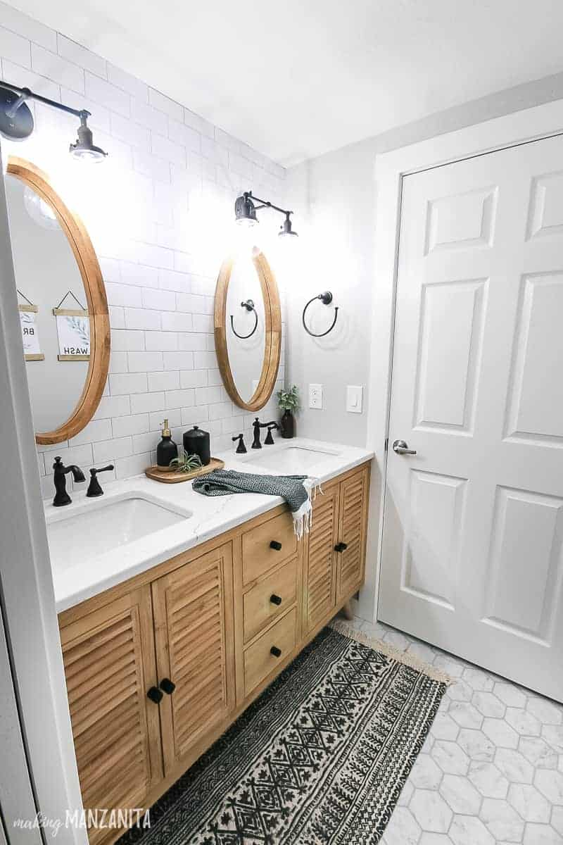 Wood vanity with black hardware, dual sinks with white countertop and subway tile backplace with mirrors and industrial style lighting