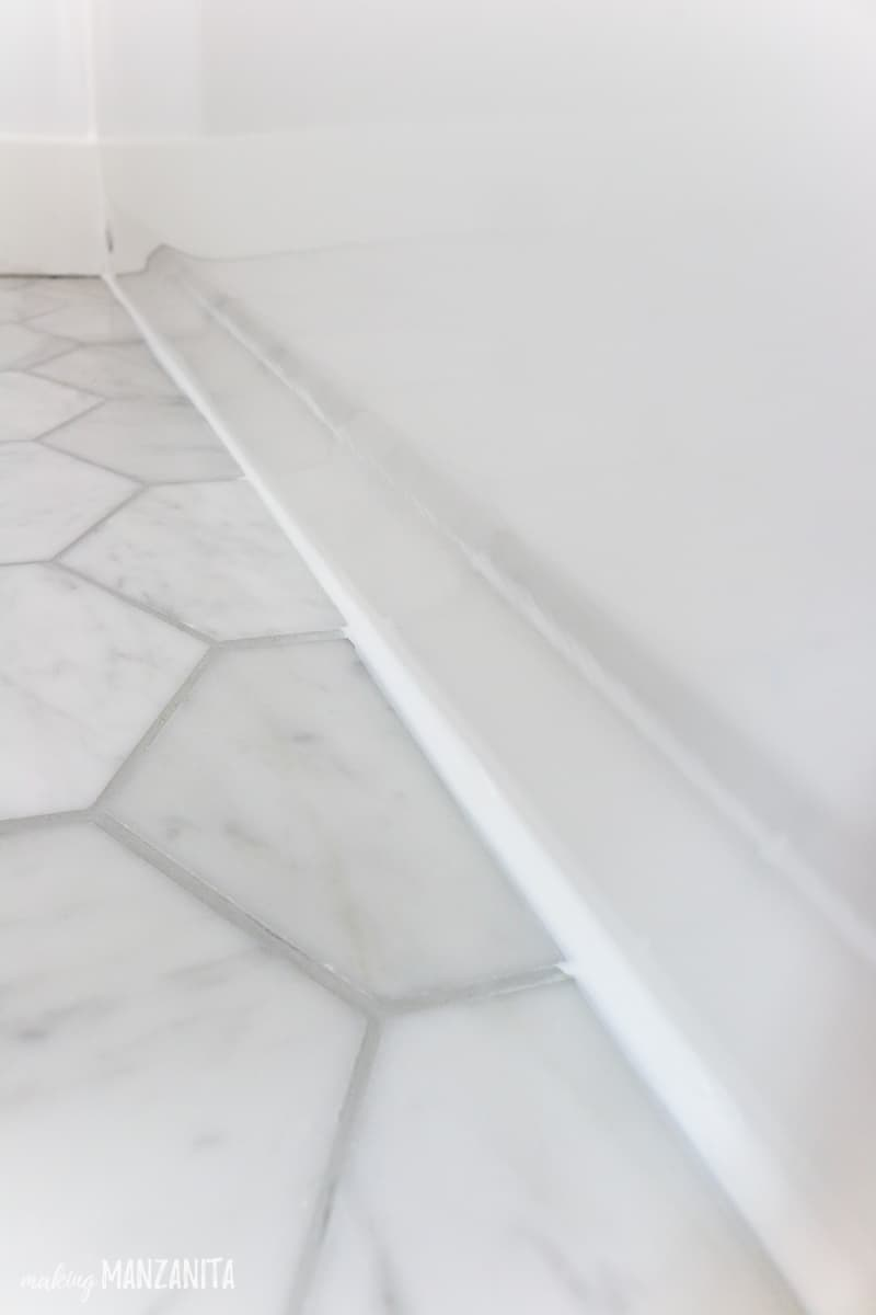 View of where marble floor tile meets the bathtub filled with white caulk to waterproof a shower