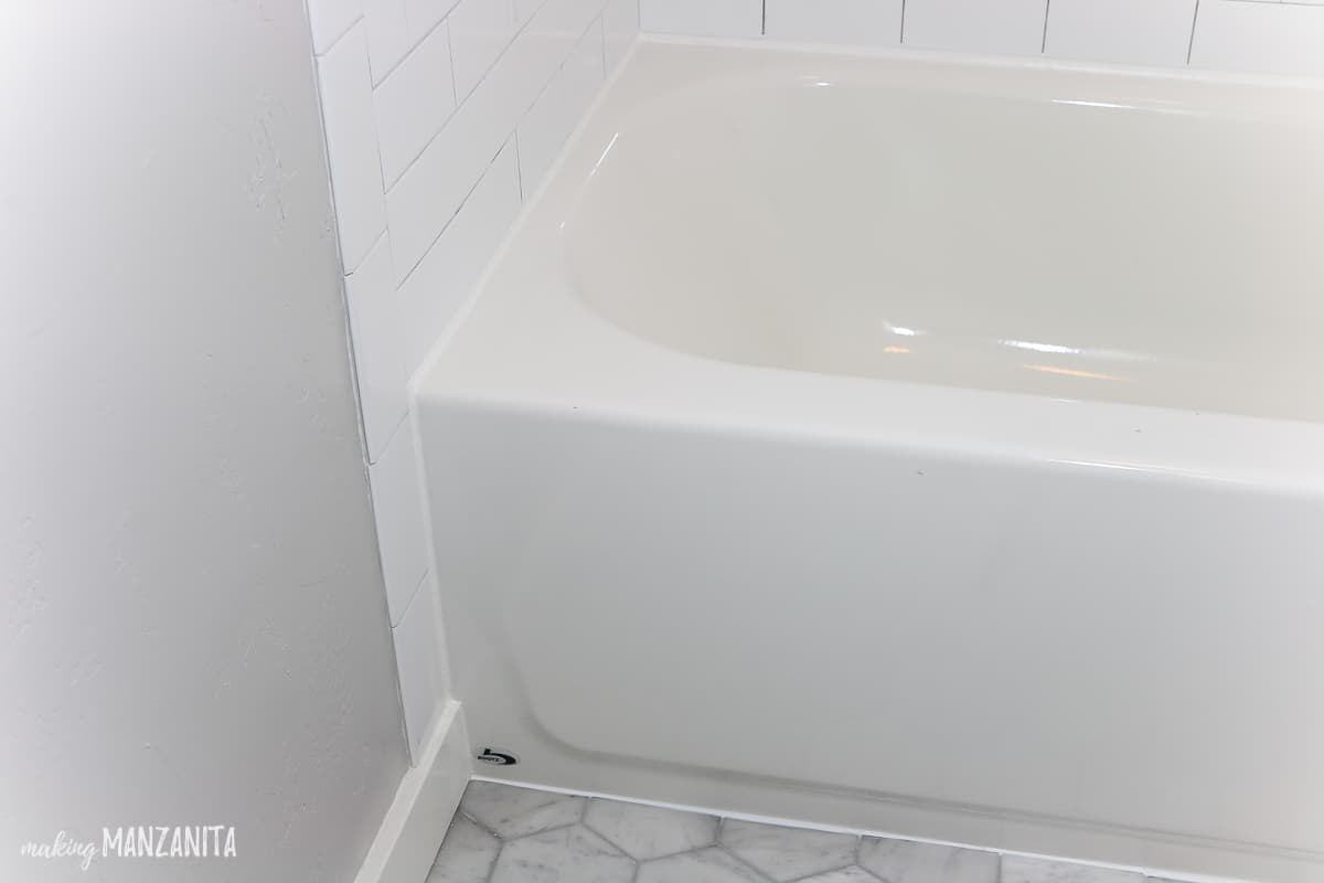Corner view of shower bath tub showing shower caulk lines