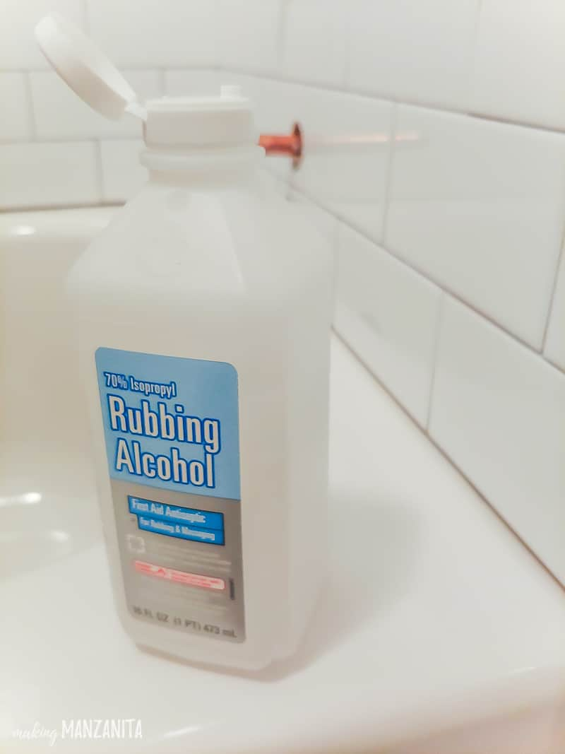 Bottle of rubbing alcohol sitting on the edge of bathtub prior to adding shower caulk