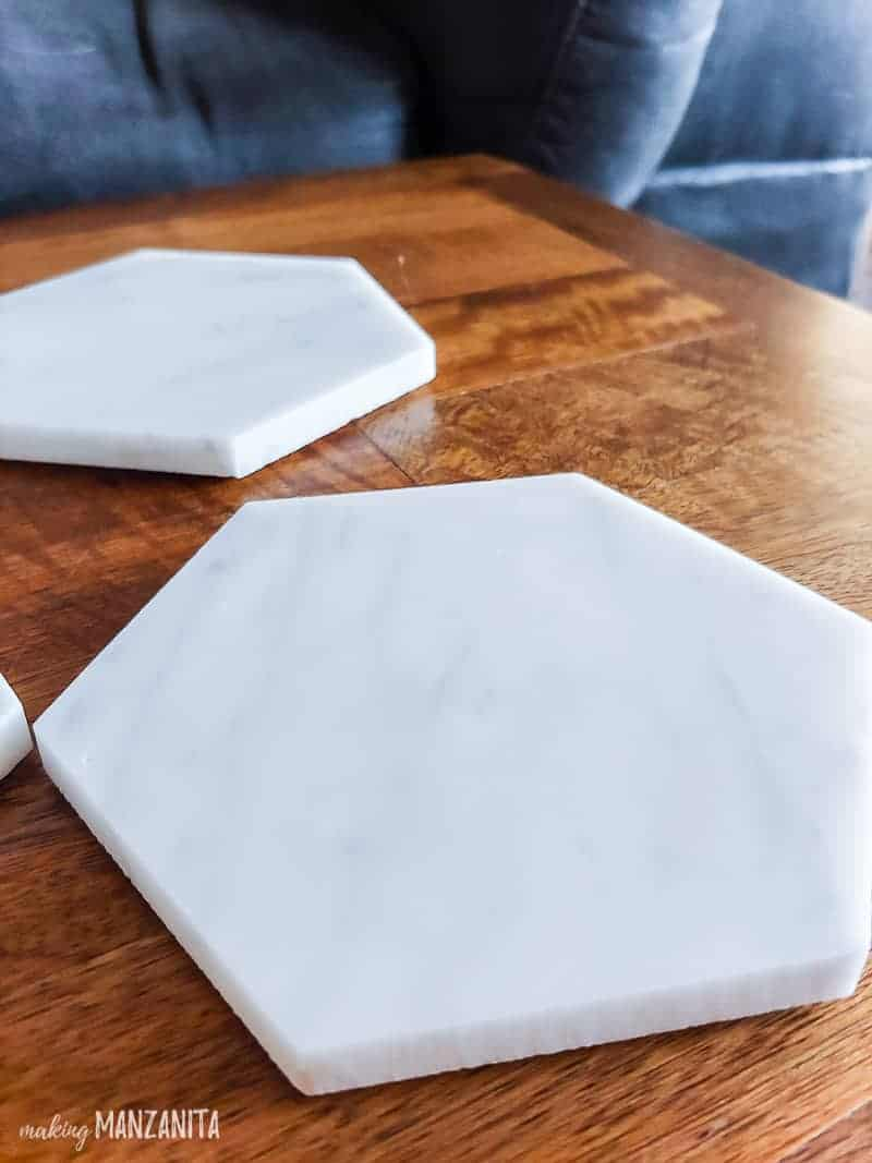 Marble tile coaster in hexagon shape sitting on wooden table