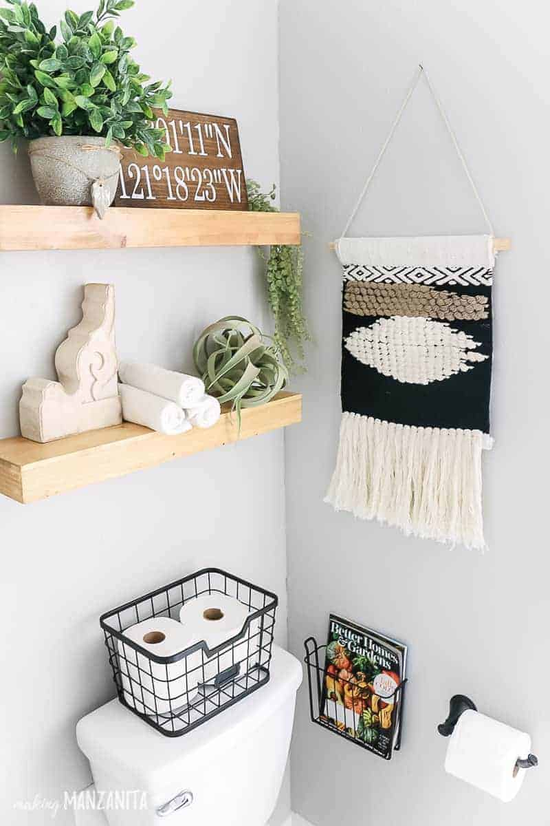 Wooden floating shelved above toilet in small bathroom with light gray walls, woven wall hanging, basket on back of toilet with toilet paper, shelves with air plant, faux palnts