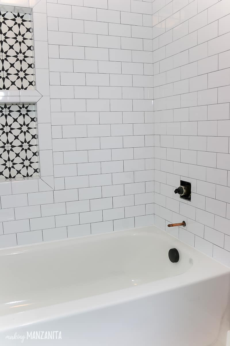 Corner of shower with white subway tile and gray grout on the walls and you can see shower niche corner