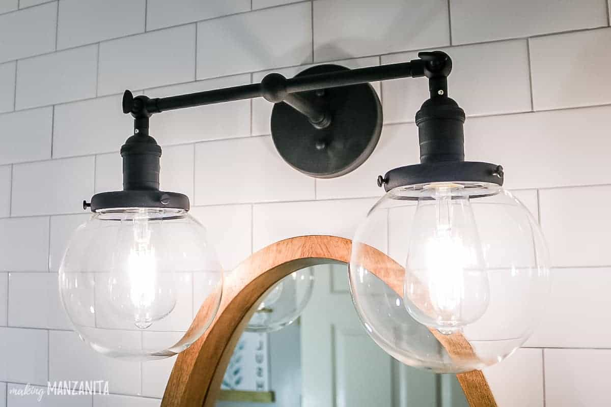 Black industrial style vanity light with 2 glass globes and daylight edison bulbs