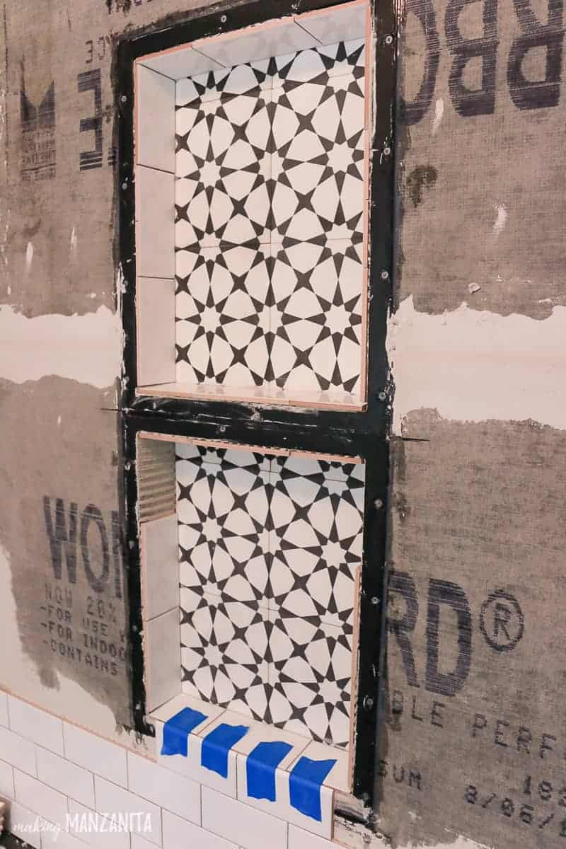 Black shower niche shelf getting installed in shower with black and white cement tiles on back and white subway tiles around.