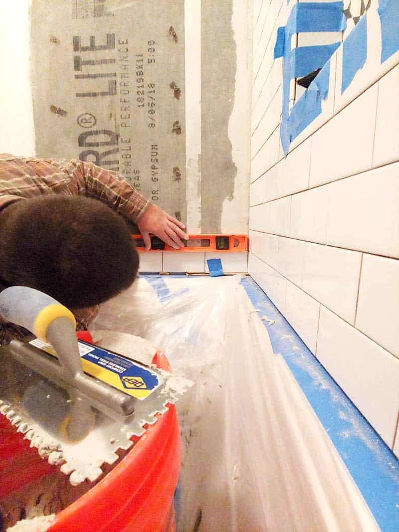 Man installing subway tile walls in shower and holding a level on top making sure it is level
