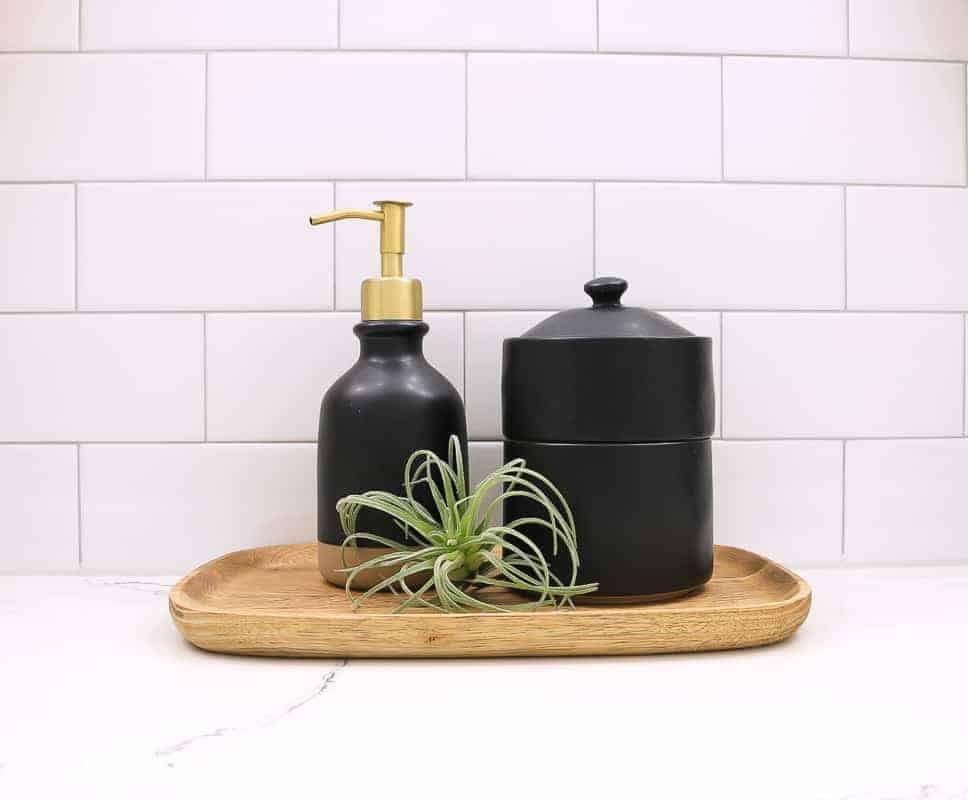 Black soap dispenser and bath canister sitting on wood tray with faux airplant on bathroom countertop with white subway tile in the background