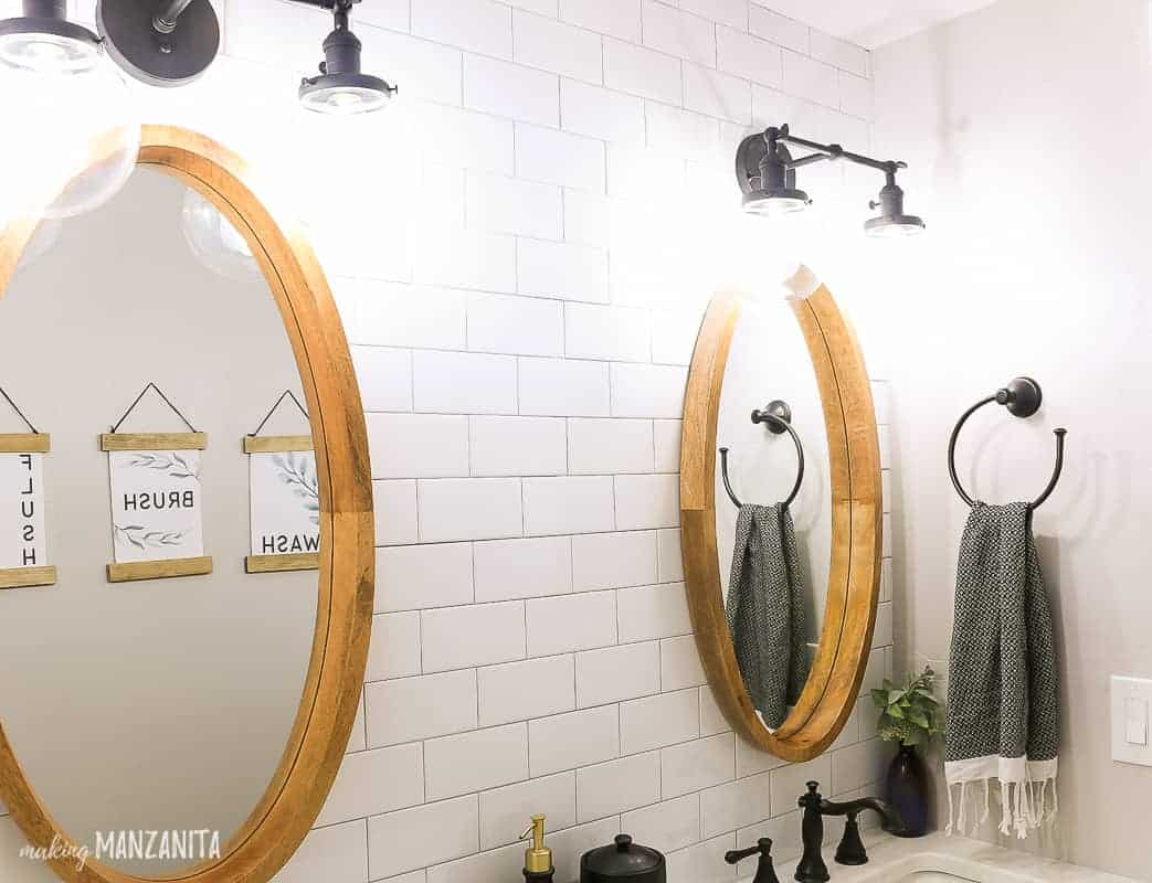 Side by side oval mirror hanging on white subway tile wall with black vanity lights hanging above over a dual sink vanity in a farmhouse bathroom