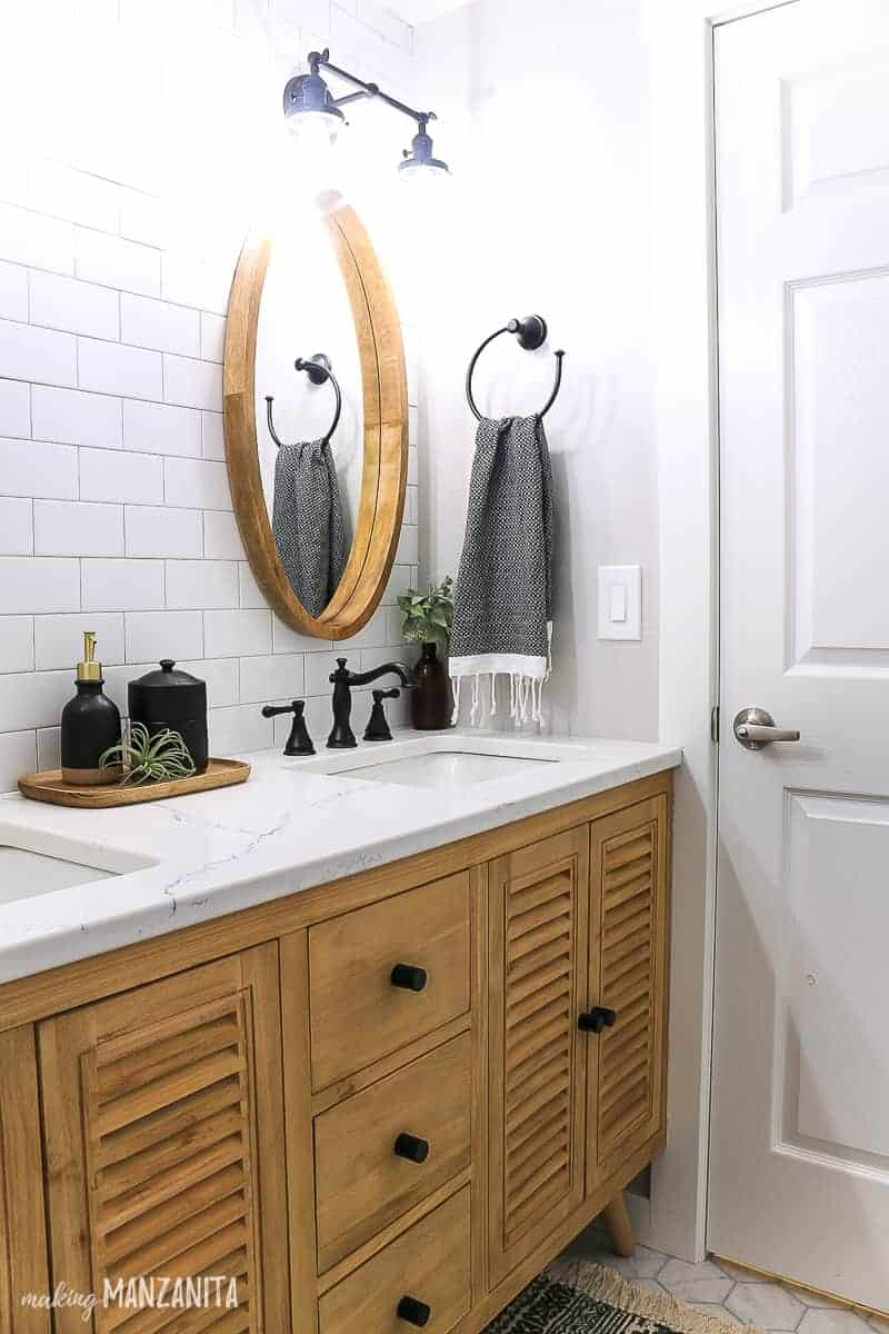 Dual sink wood vanity with shutter door fronts and slim black hardware with a white quartz countertop, white subway tile mirror and round wood mirrors in a farmhouse bathroom