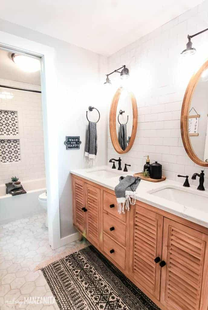 shows a boho styles bathroom with white marble hexagonal tile floors with a white and black boho run and a wood cabinet with white marble sink counter and white tile walls.