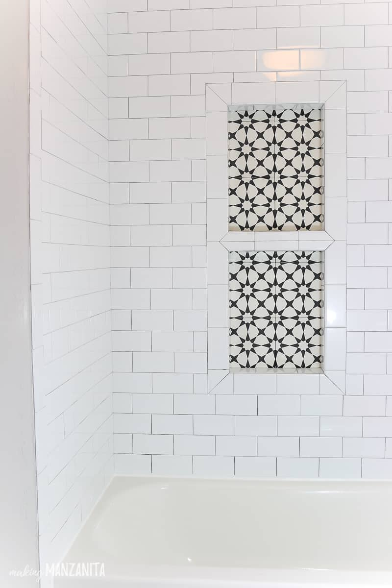 Modern farmhouse shower niche to hold shampoo bottles with black and white decorative tile on back and white subway tile shower walls