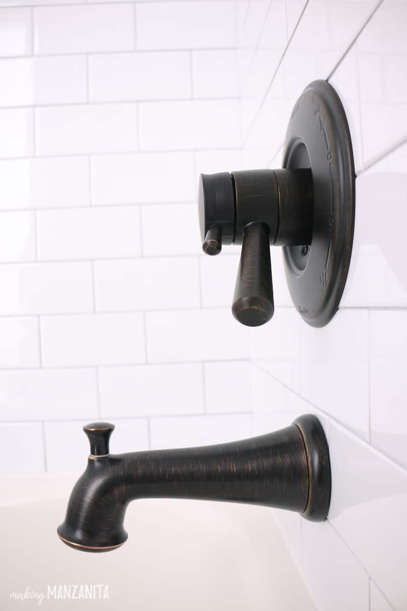 Side view of an oil rubbed bronze bath tub faucet in a shower/bath with white subway tile on walls