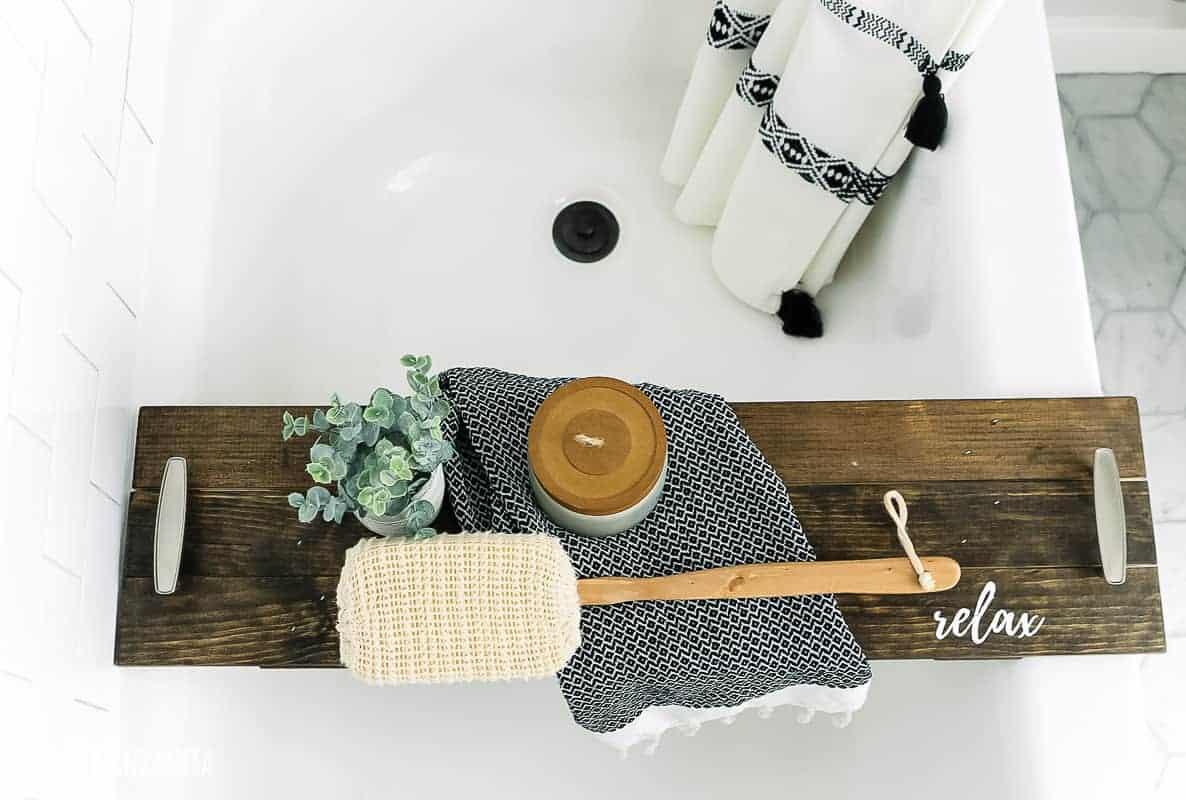 Wood bath tub tray that says relax on it in the corner sitting in tub with loofah, candle, towel and faux plant staged
