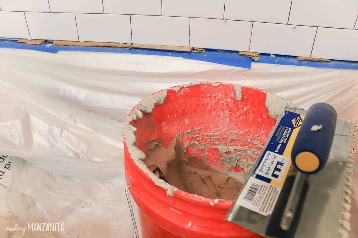 Bucket of thinset mortar sitting in a bathtub with a trowel sitting on it while white subway tile gets installed on shower walls