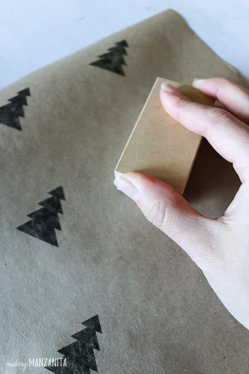 Hand stamping black Christmas tree on sheet of brown kraft paper for DIY wrapping paper