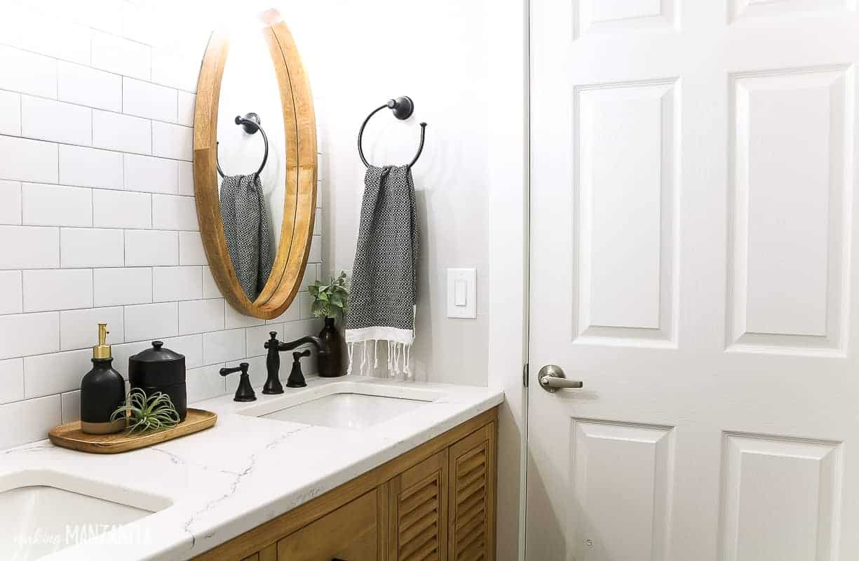 White quartz countertop that looks like marble in a modern farmhouse bathroom with white subway tile backsplash and round wood framed mirror