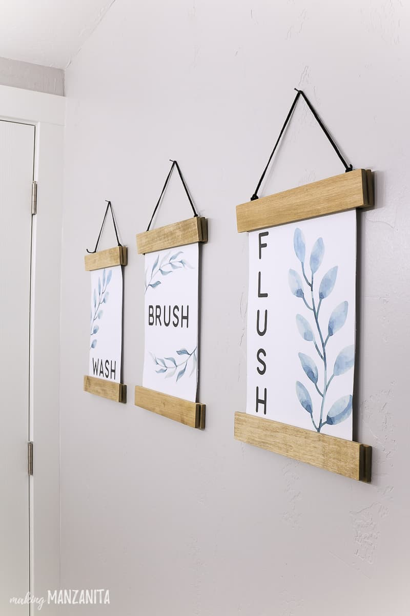 Three side by side wall decor printables with wash brush flush on them with leaves and floral designs hanging in DIY wood frames on a wall in a farmhouse bathroom