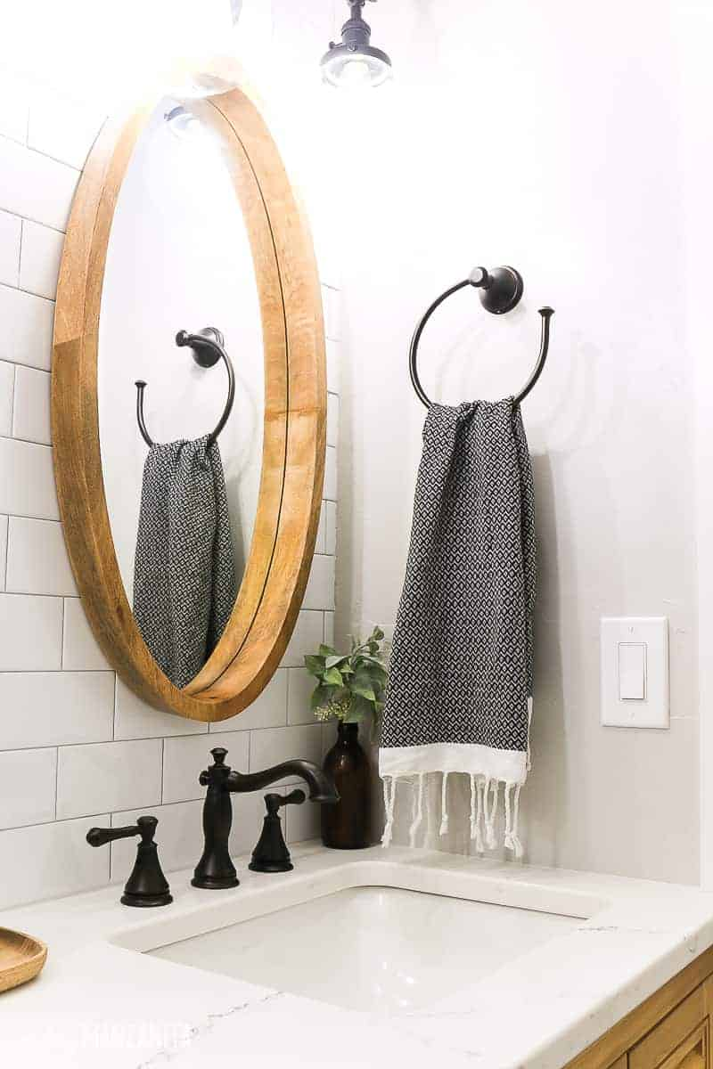 Wood framed oval mirror mounted on white subway tile wall over a vanity with oil rubbed bronze sink faucet and white quartz counter top with vanity light above it. Black turkish towel hanging on towel ring on wall
