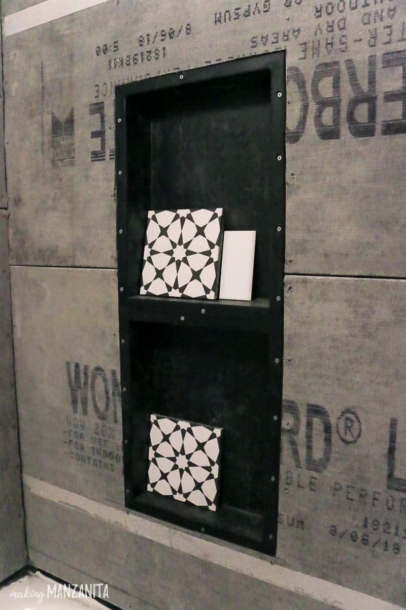 Black prefabricated shower niche insert installed in between the studs with tile samples sitting inside