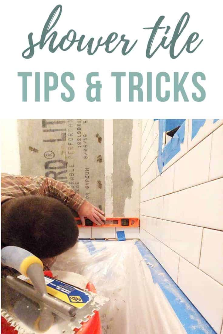 Man installing shower wall tile and leveling the bottom row with text overlay that says shower tile tips & tricks