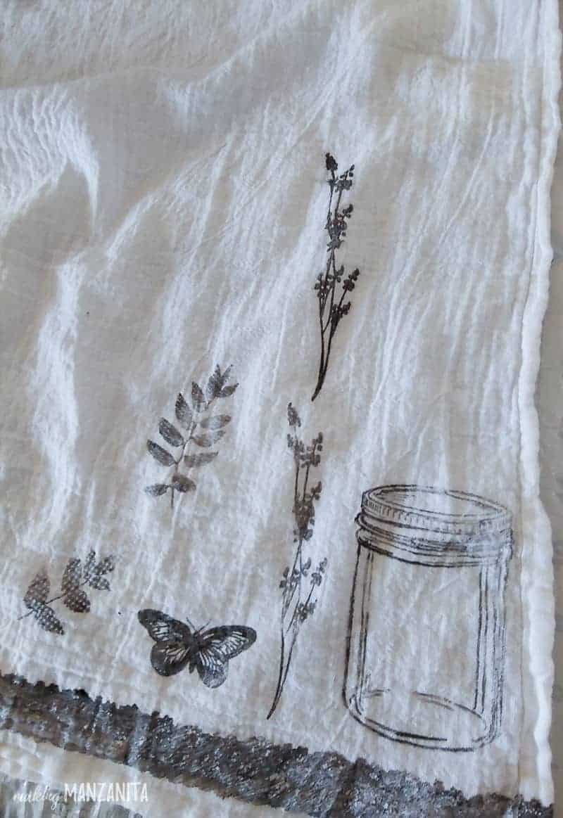 The corner of a flour sack cloth with a few designs stamped on with black fabric paint to be used as a tester towel