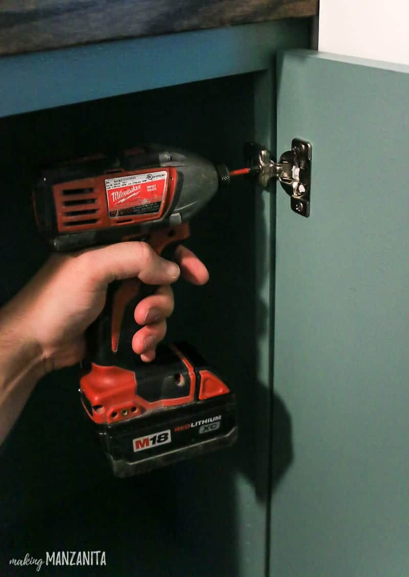 Man installing metal soft close hinges on the inside of a cabinet door with a drill