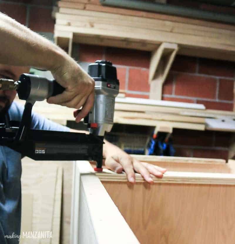 Man attaching front face to cabinet with nail gun